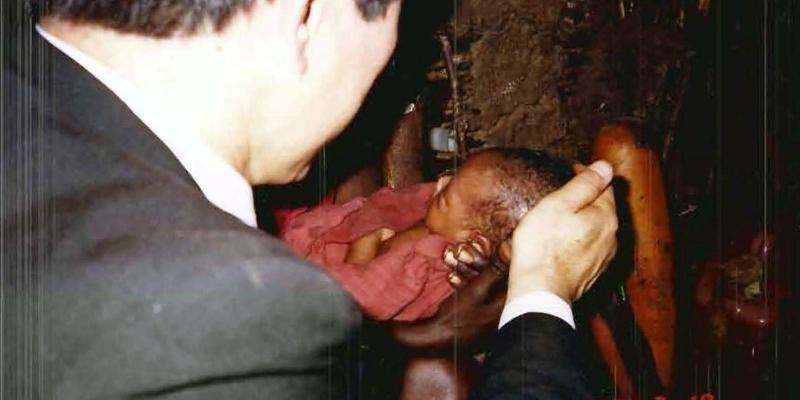 1988 - 케냐 맛사이족<br> 맛사이 성도 소똥집 안에서, 여성도의 신생아를 안고 축복기도하는 김정복 목사